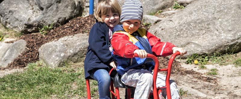 Dieses Bild zeigt zwei fröhliche Kinder aus der AWO Kita Münchberg auf einem Dreirad