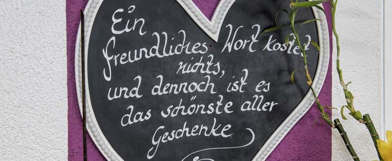 """Dieses Bild zeigt eine Tafel in Herzform auf der steht """"Ein freundliches Wort kostet nichts und dennoch ist das schönste aller Geschenke"""""""